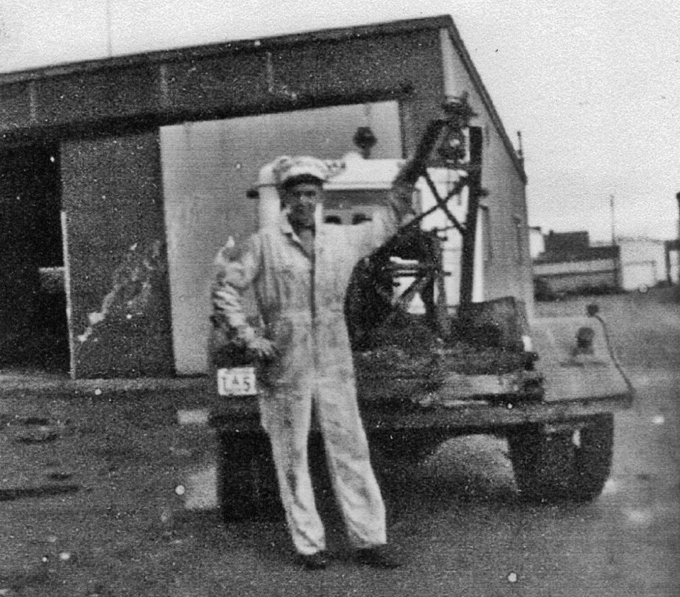 Earl Rose stands behind the 1934 Chevrolet tow truck in the ally behind Brenno's, auto repair shop on the left. Brenno family photo.